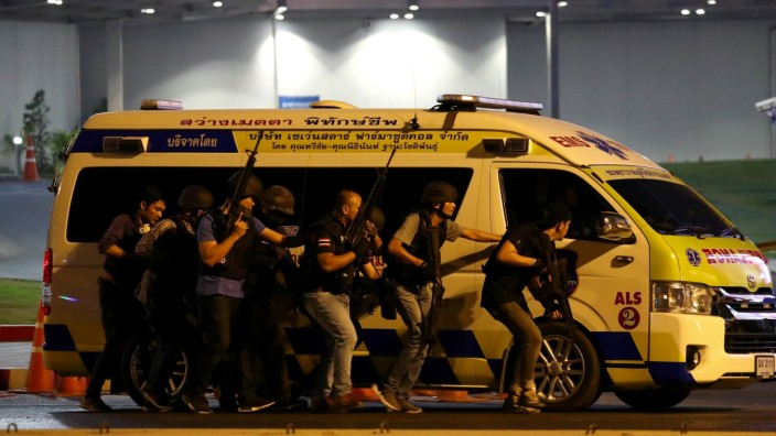 Thai security forces take cover behind an ambulance as they chase a shooter hidden in a shopping mall after a mass shooting in front of the Terminal 21, in Nakhon Ratchasima, Thailand