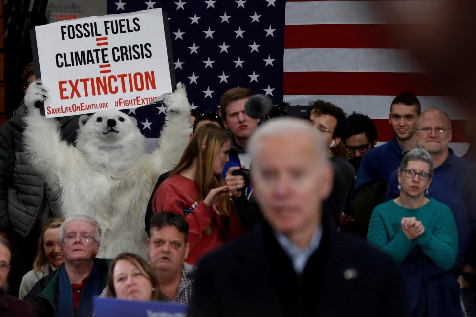 A person dressed as a polar bear holds a sign as Democratic 2020 U.S. presidential candidate and former vice president Joe Biden speaks during a campaign event in Hudson, New Hampshire U.S.