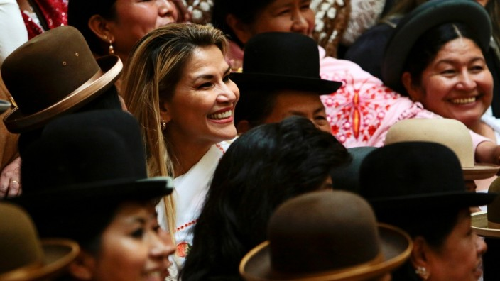Bolivia's interim President Jeanine Anez poses for a photo during an event with indigenous Bolivian women known as 'Cholas' in La Paz