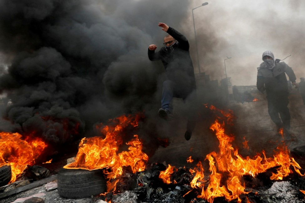 A Palestinian demonstrator jumps over burning tires during a protest against Trump's Middle East peace plan and in support of President Abbas, near the Jewish settlment of Beit El in the Israeli-occupied West Bank