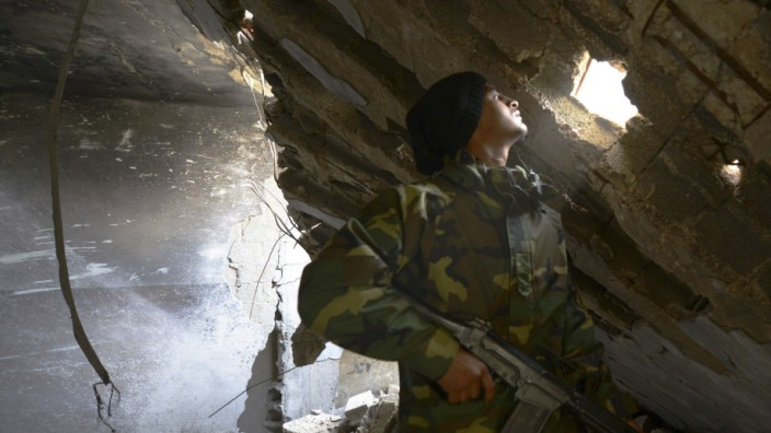 A member of Libyan pro-government forces, backed by locals, holds his weapon as he looks through hole in wall, during clashes with Shura Council of Libyan Revolutionaries, in Benghazi