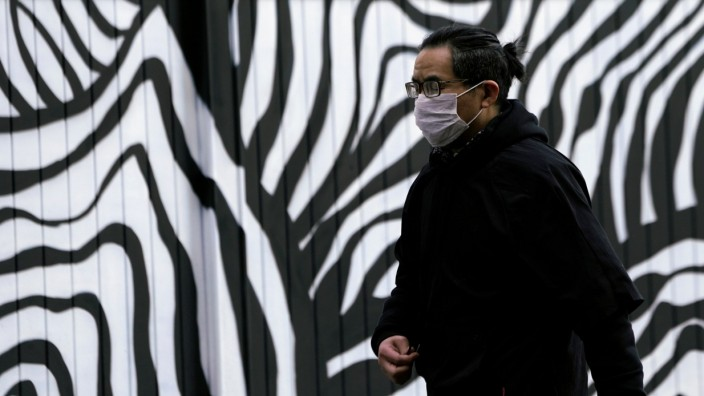 A man wearing a mask is seen in front a wall painted with graffiti at a construction site in Shanghai
