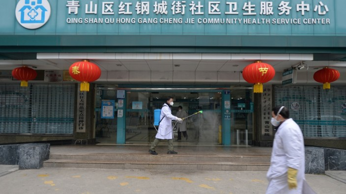 Doctor disinfects the entrance of a community health service center in Wuhan