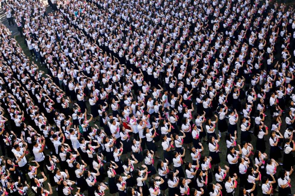 Thousands of Filipino students dance to take part in the One Billion Rising global campaign to end violence against women and children, during the Valentine's Day celebration at St Scholastica's College in Manila