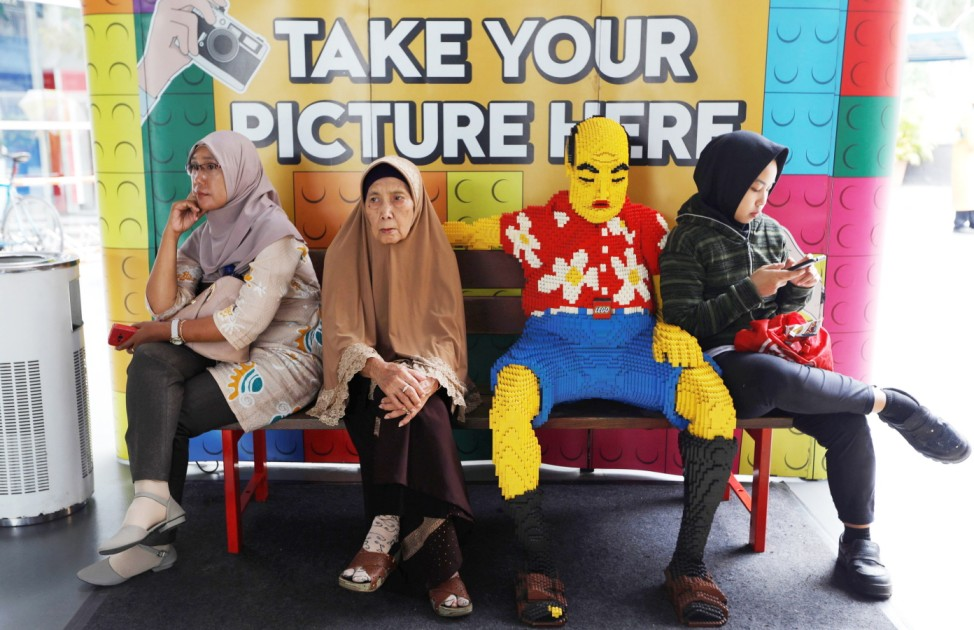 Women sit on a bench next to a Lego decoration inside a shopping mall in Jakarta