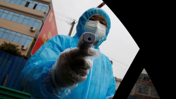 FILE PHOTO: A medical worker holds a thermometer to check a passenger's temperature at a checkpoint as the country is hit by an outbreak of the novel coronavirus in Susong County
