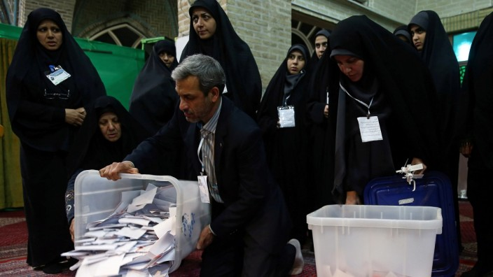 Poll workers empty full ballot boxes after the parliamentary election voting time ended in Tehran