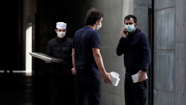 Workers wearing face masks are seen at the theatre where the Italian designer Giorgio Armani said his Milan Fashion Week show would take place in Milan