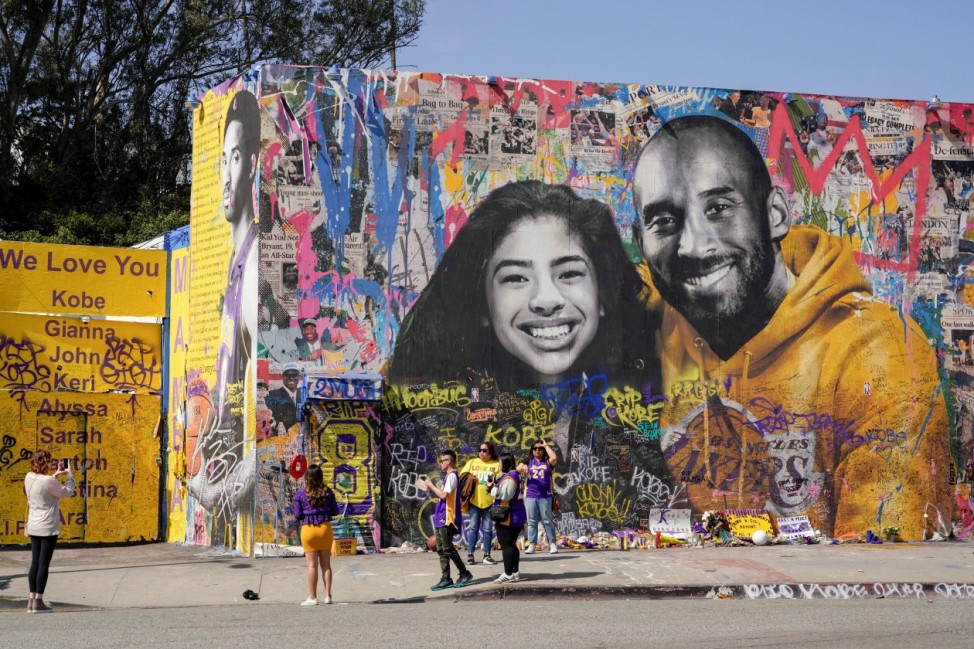 Fans gather around a mural of late NBA great Kobe Bryant and his daughter Gianna Bryant during a public memorial for them and seven others killed in a helicopter crash, at the Staples Center in Los Angeles