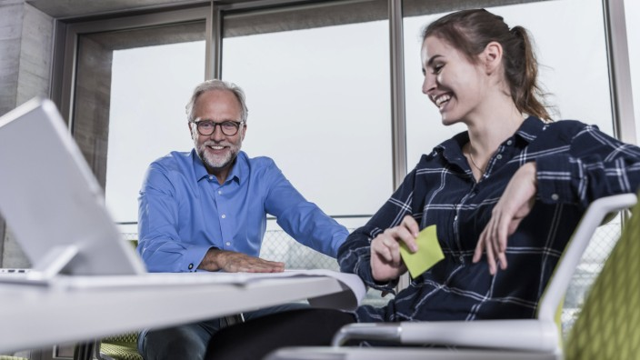 Smiling mature businessman and young woman with tablet in conference room in office model released S