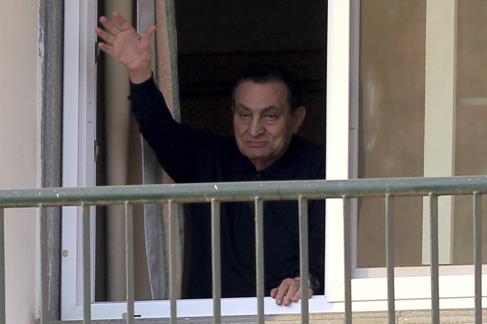 FILE PHOTO: Ousted Egyptian president Hosni Mubarak waves to his supporters outside the area where he is hospitalized during his birthday at Maadi military hospital on the outskirts of Cairo
