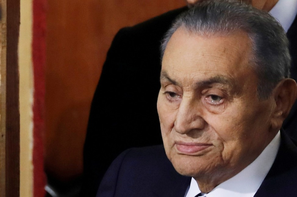 FILE PHOTO: Former Egyptian President Hosni Mubarak arrives with his son Gamal in a court case accusing ousted Islamist president Mohamed Mursi of breaking out of prison in 2011, in Cairo