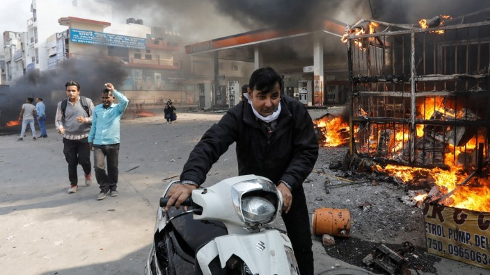 A man pushes his damaged scooter past a burning petrol pump during a clash between people supporting a new citizenship law and those opposing it, in New Delhi