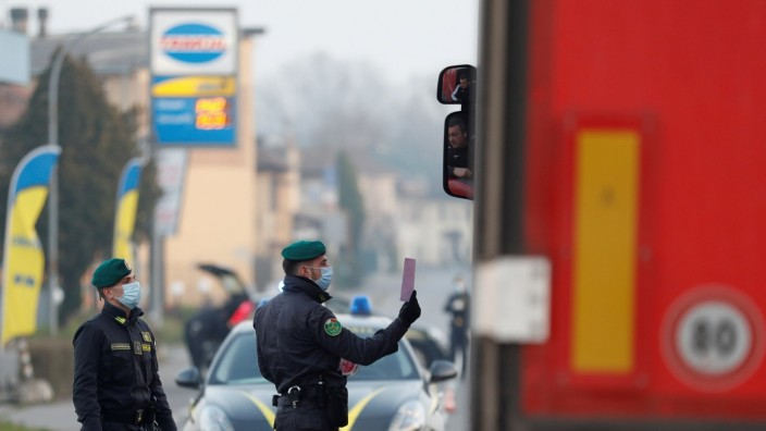 FILE PHOTO: Members of the Guardia di Finanza wearing face masks stop a car, amid a coronavirus outbreak in northern Italy, in Casalpusterlengo