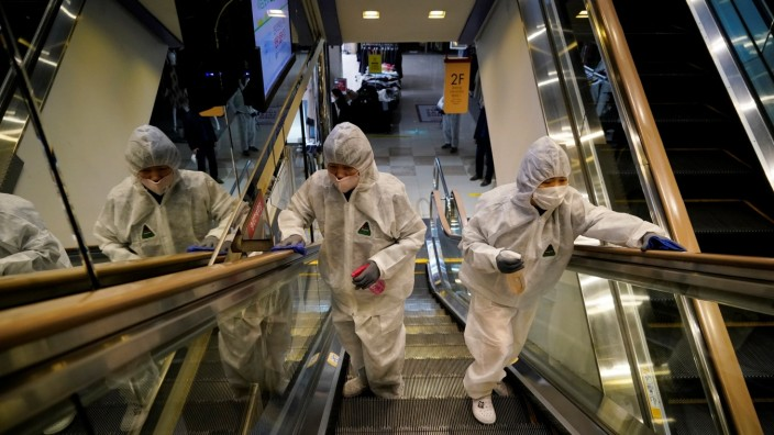 Employees from a disinfection service company sanitize at a department store in Seoul