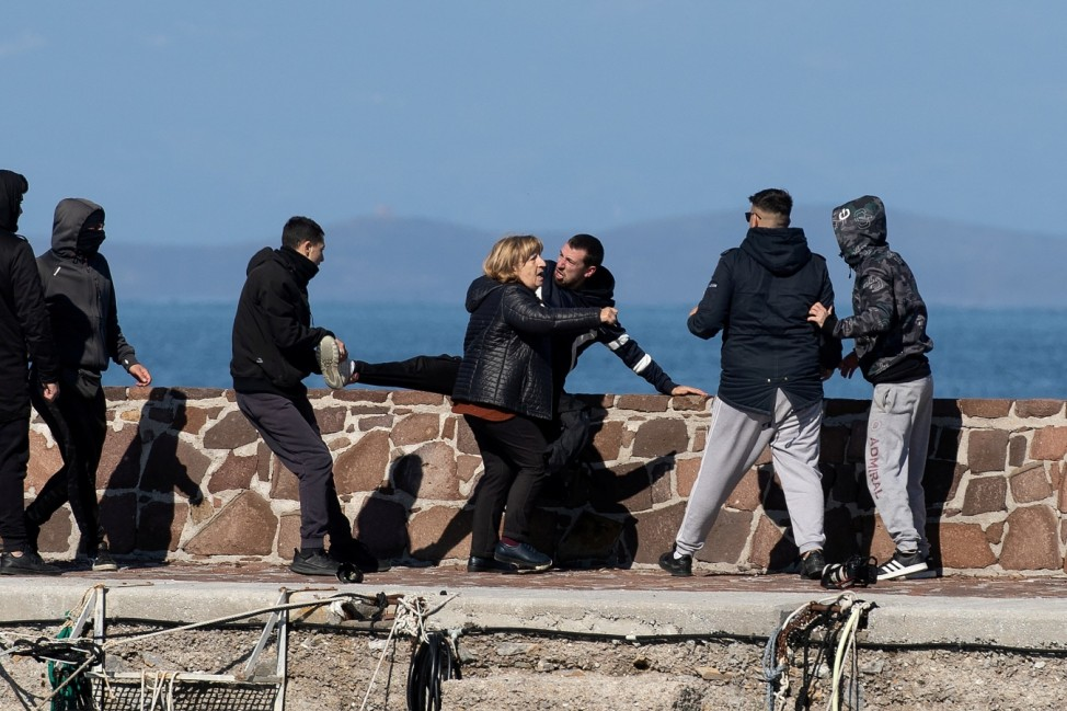 Locals who prevent migrants on a dinghy from disembarking at the port of Thermi beat a journalist, as a woman tries to stop them, on the island of Lesbos, Greece