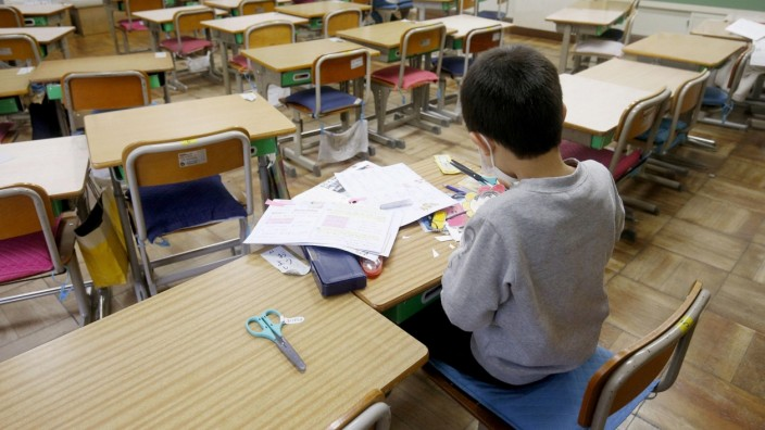 Two students do self-study at an elementary school where the facility was opened for children who cannot stay at home alone while their parents are at work, in Saitama, Japan