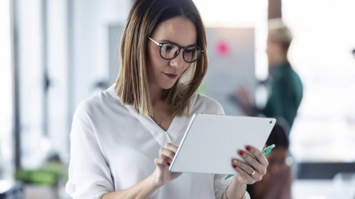 Female entrepreneur using digital tablet in office model released Symbolfoto property released PUBLICATIONxINxGERxSUIxAU