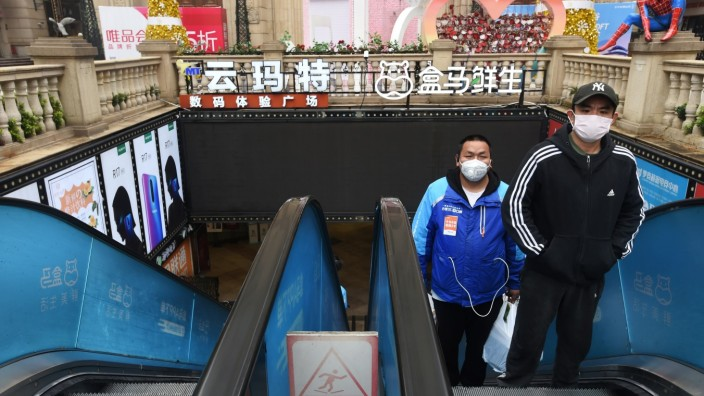 Delivery worker for Alibaba's Hema Fresh wearing a face mask rides on an escalator behind a man at a shopping complex in Wuhan