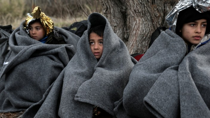 FILE PHOTO: Children huddle under blankets after migrants arrived by dinghy on a beach on the Greek island of Lesbos