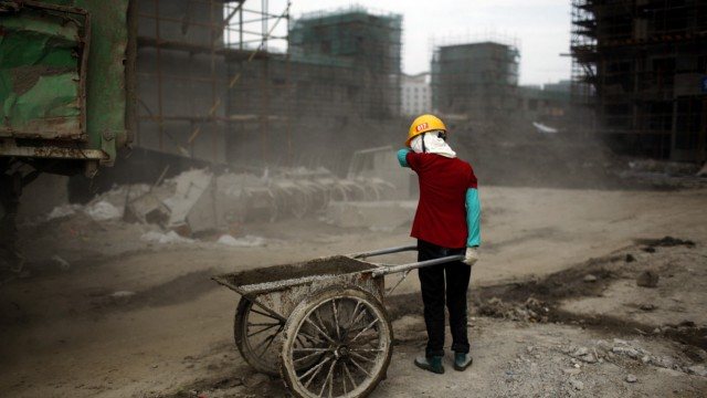 Ou Mei, a 45-year-old female migrant construction worker, shields her face from dust during a shift at a residential construction site in Shanghai
