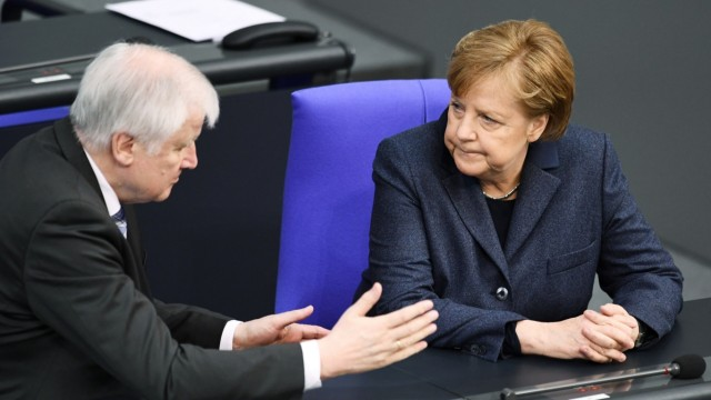 German Chancellor Angela Merkel and Interior Minister Horst Seehofer attend a plenum session at the lower house of parliament, Bundestag, in Berlin