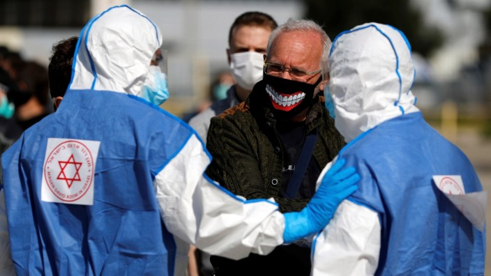 An Israeli man wearing a mask chats with paramedics wearing protective suits near a dedicated polling station where Israelis under quarantine from the coronavirus can vote in Israel's national election, in Haifa, Israel