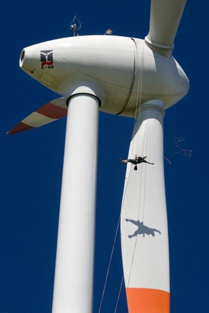 Industriekletterer pruefen Aussenhaut eines Windkraftanlagenrotors