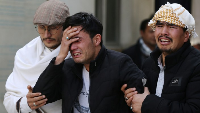 Afghan men cry at a hospital after they heard that their relative was killed during an attack in Kabul, Afghanistan