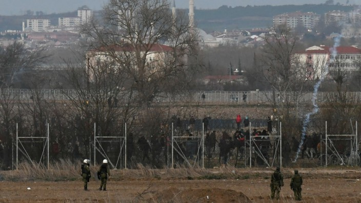 Greek riot police officers stand guard, as migrants are seen on the other side of the border fence, with the city of Edirne seen in the background, in Kastanies
