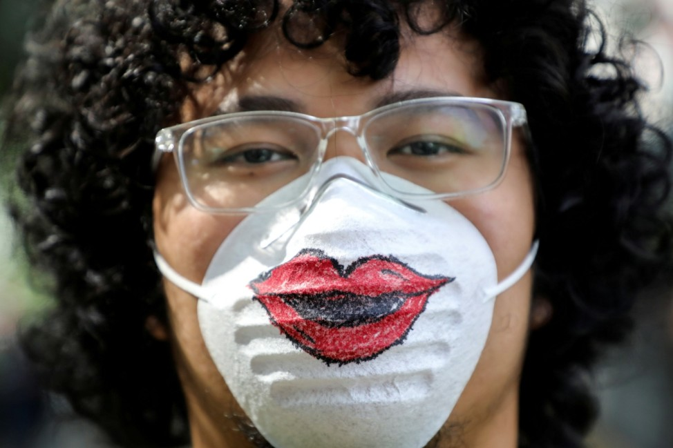 A man wearing a protective mask that features a pair of lips poses for a picture during a Women's March to mark International Women's Day in Kuala Lumpur