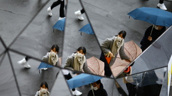 A woman wearing a protective face mask, following an outbreak of the coronavirus disease (COVID-19), is reflected in mirrors in Tokyu Plaza Omotesando Harajuku shopping center in Tokyo