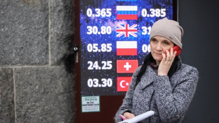 A woman stands near a board showing currency exchange rates in central Kiev