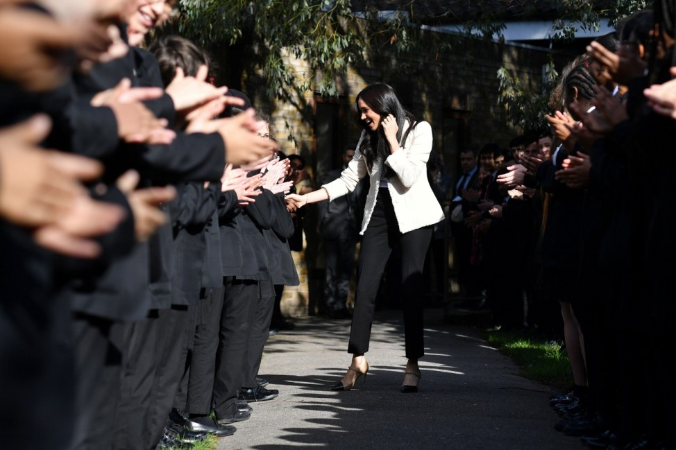 Britain's Meghan, Duchess of Sussex, smiles as she is welcomed by students to visit the Robert Clack School in Essex