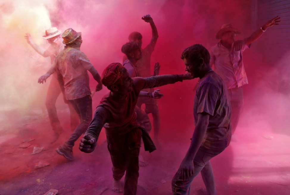 People dance as they throw coloured powder at each other during Holi celebrations in Kolkata