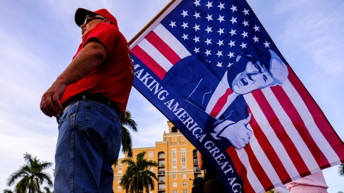 Supporters of U.S. President Donald Trump wave Trump banners outside the location of Democratic U.S. presidential candidate Michael Bloomberg's Super Tuesday rally, in West Palm Beach