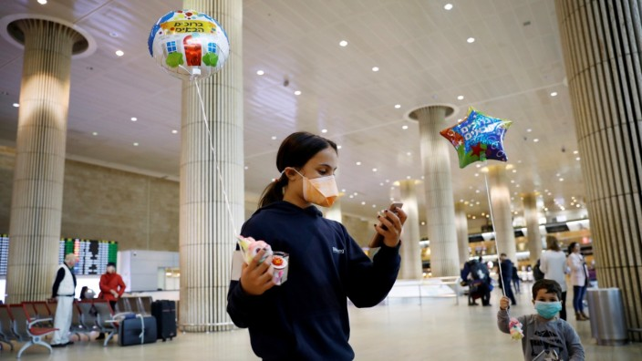 Children hold balloons in the arrivals terminal at Ben Gurion International airport in Lod, near Tel Aviv