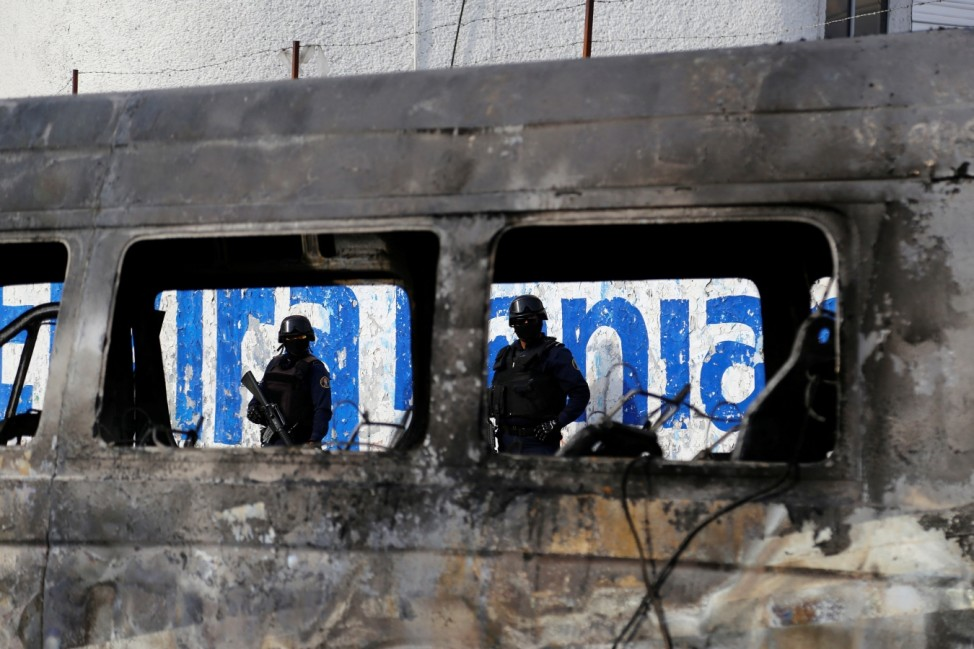 Police stand near the wreckage of a car that was burnt in a blockade set by members of the Santa Rosa de Lima Cartel to repel security forces during a police operation on the outskirts of Celaya