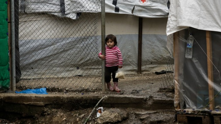 A girl stands among makeshift shelters at a camp for refugees and migrants next to the Moria camp, on the island of Lesbos
