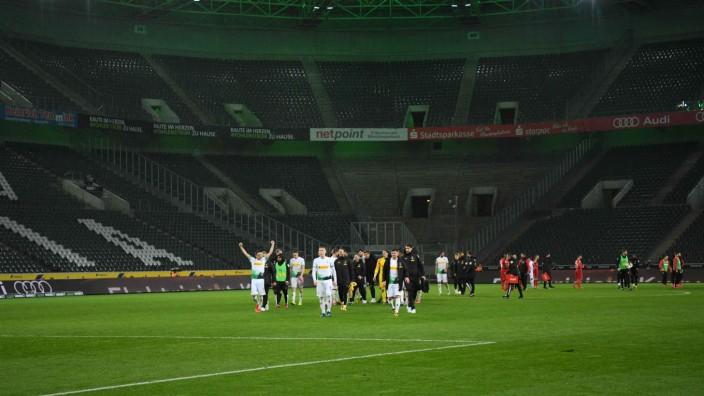 Geisterspiel in Gladbach: Gladbachs Spieler machen sich nach dem Spiel auf den Weg zu den Fans, die vor dem Stadion warten.