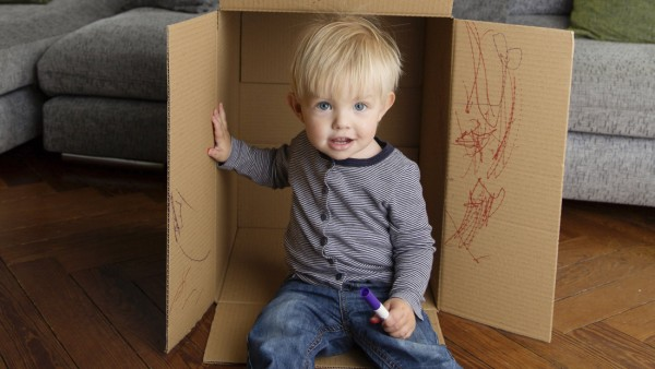 Smiling toddler sitting in a cardboard box at home model released Symbolfoto property released PUBLI
