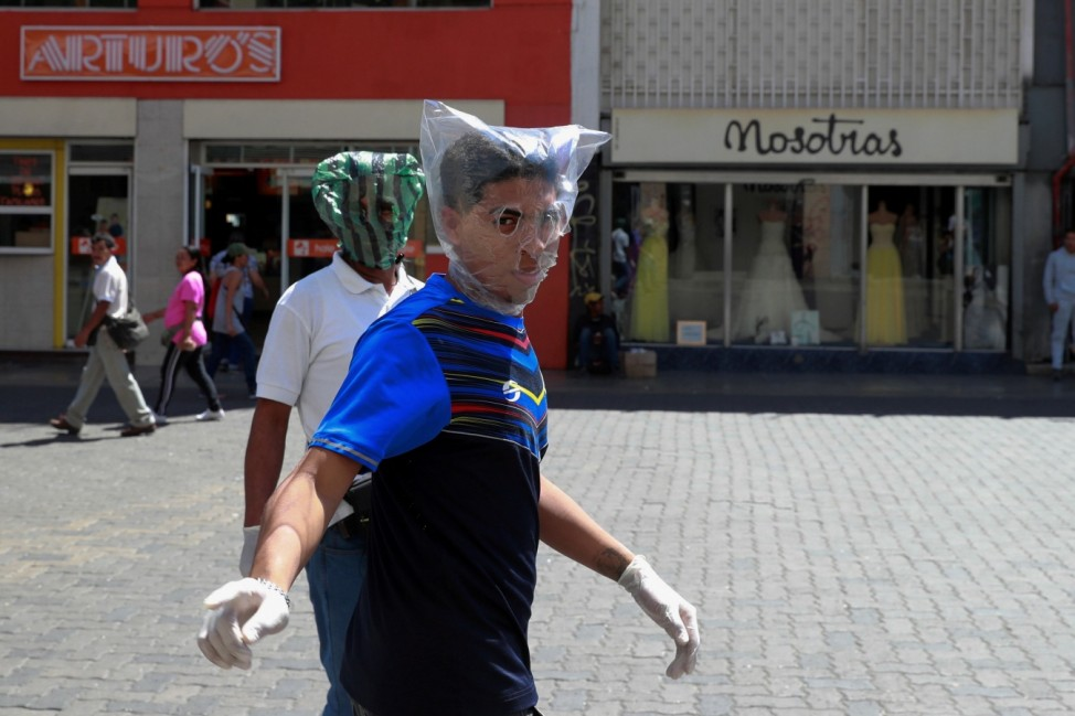Men cover their faces with plastic bags in response to the spreading coronavirus (COVID-19) in Caracas