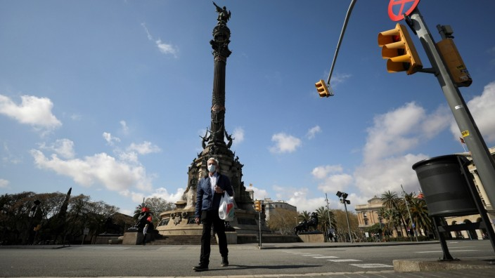 Man wears a protective face mask as he walks along an empty The Columbus Monument, amidst concerns over Spain's coronavirus outbreak, in Barcelona