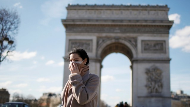 A woman wearing a protective mask, walks near Arc de Triomphe as France grapples with an outbreak of coronavirus (COVID-19) disease, in Paris