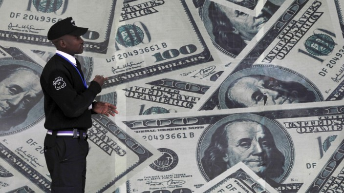 A security guard walks past a montage of U.S. dollar bills outside a currency exchange bureau in Nairobi