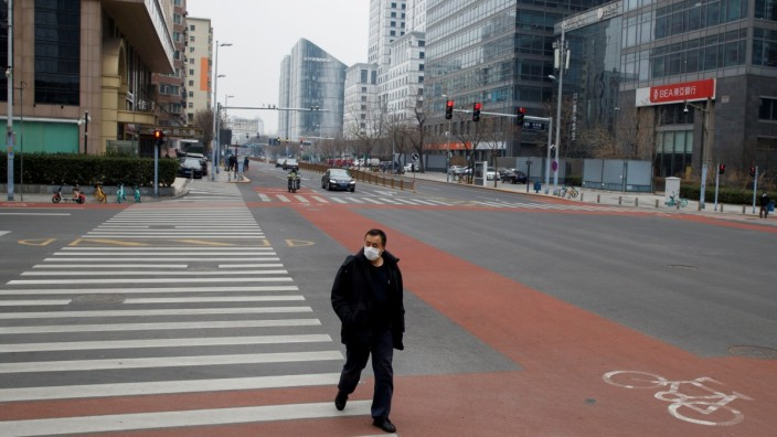 FILE PHOTO: A man wears a face mask as he crosses a street in the Central Business District in Beijing as the country is hit by an outbreak of the novel coronavirus