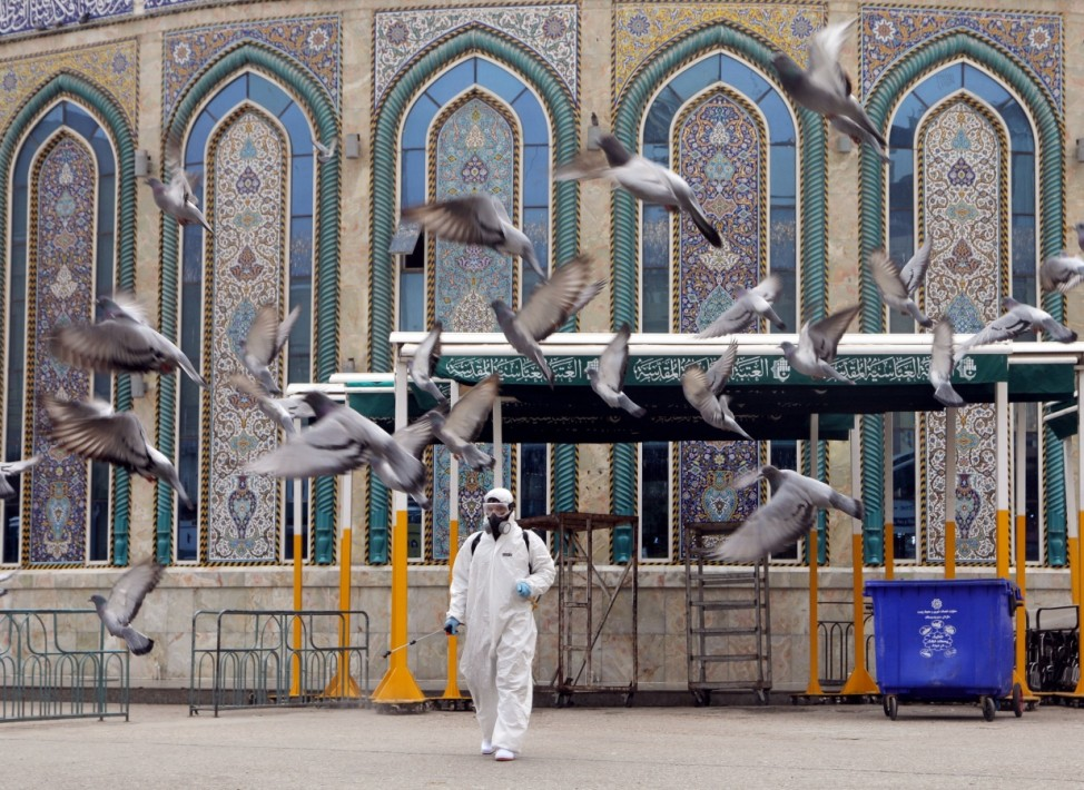 A worker in a protective suit sprays disinfectants near Imam Abbas shrine as a precaution against the coronavirus, following the outbreak, in the holy city of Kerbala