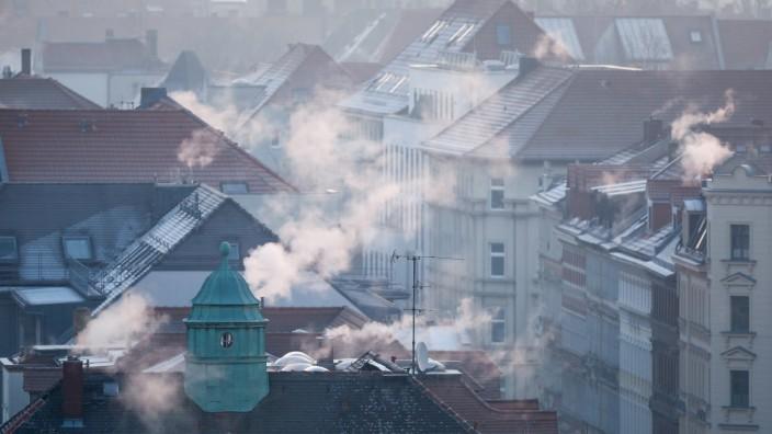Treibhausgase und CO2: Rauch steigt aus Wohnhäusern auf