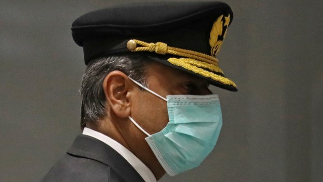 A pilot wearing a mask arrives at the international lounge at Pearson Airport in Toronto