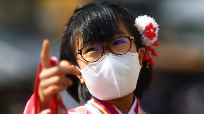A kimono-clad girl, wearing a protective mask following an outbreak of the coronavirus disease (COVID-19), gestures on a street of Gion district in Kyoto